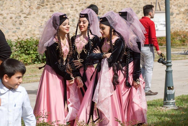 Las muchachas georgianas jovenes felices en vintage se visten con velos emotionaly que hablan durante festival fotos de archivo libres de regalías