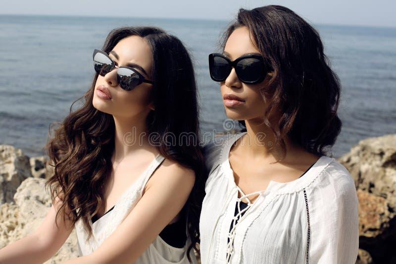 Las muchachas hermosas con el pelo oscuro llevan la ropa elegante casual y las gafas de sol foto de archivo