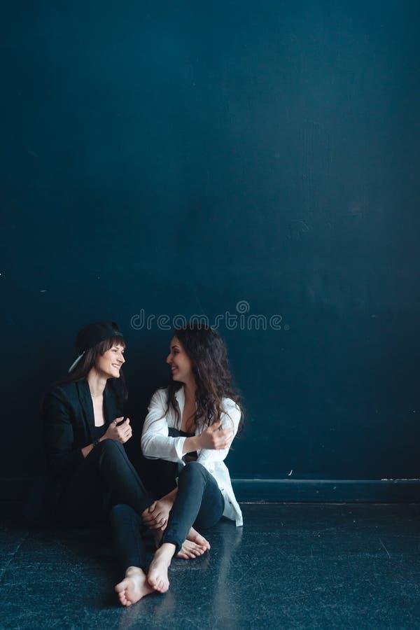 Las muchachas hermosas se sientan por la pared y la actitud fotos de archivo