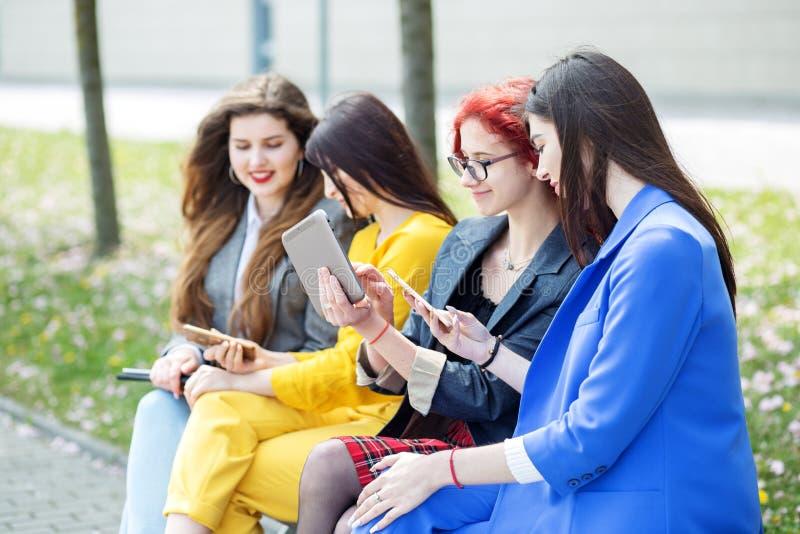 Las muchachas hermosas se sientan y charlan con los artilugios en el banco El concepto de Internet, de las redes sociales, del es imágenes de archivo libres de regalías