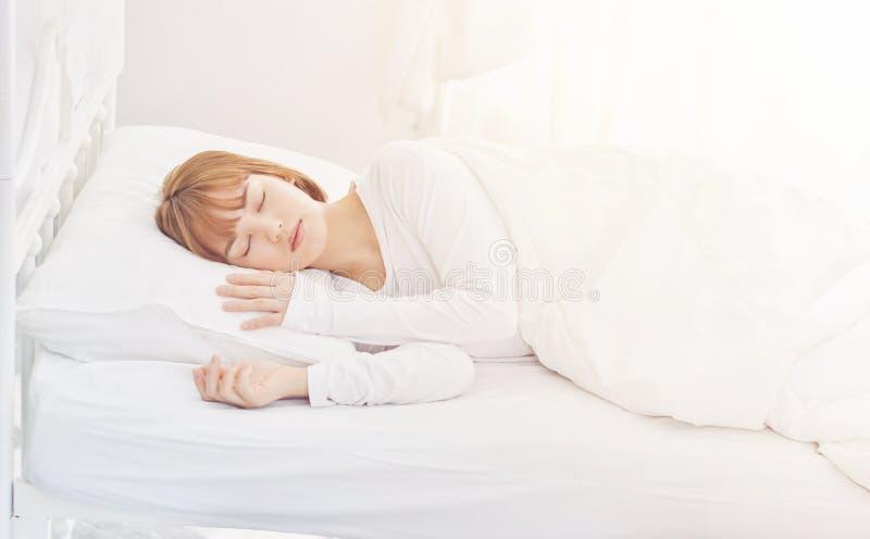Las muchachas llevan los pijamas blancos El dormir en la cama fotografía de archivo libre de regalías