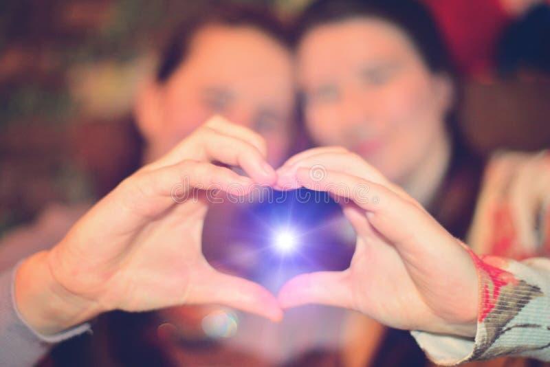 Las muchachas mueven de un tirón el corazón con sus manos El sol azul brilla de las manos El concepto de amor y de alegría imágenes de archivo libres de regalías