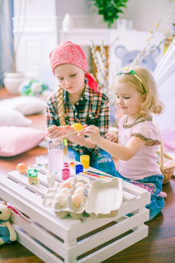 Las muchachas preciosas de la hermana pintan los huevos y se divierten que se prepara para Pascua fotografía de archivo libre de regalías