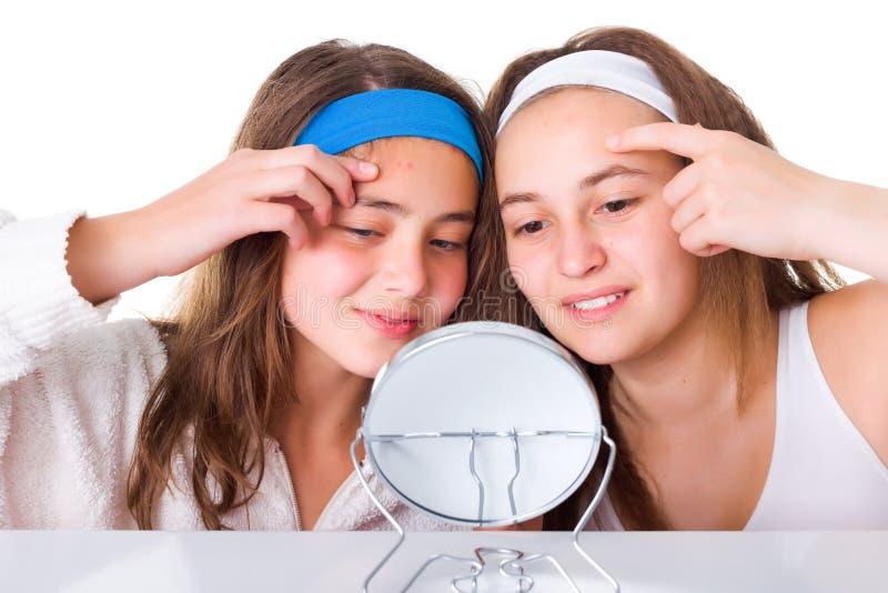 Las muchachas que buscan para los defectos en los suyos pelan foto de archivo