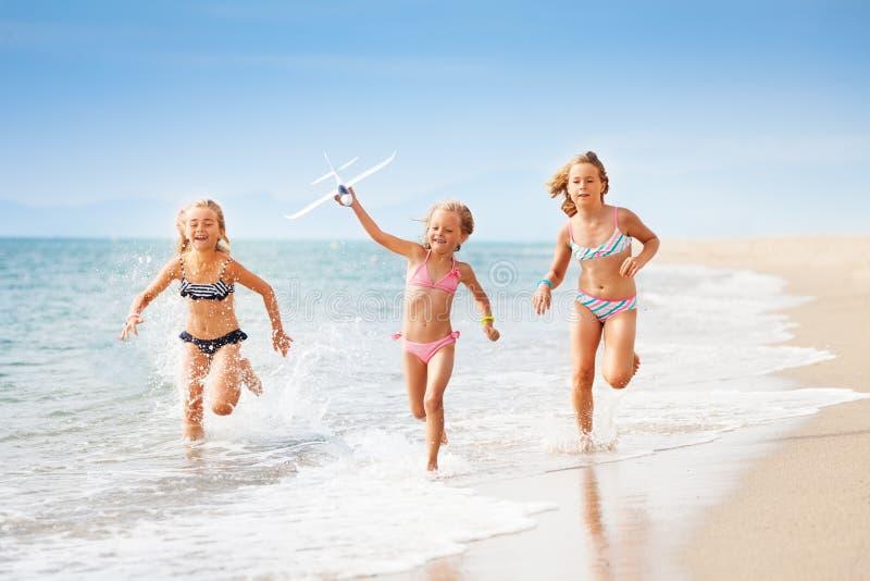 Las muchachas que corren con el aeroplano modelan en la costa foto de archivo