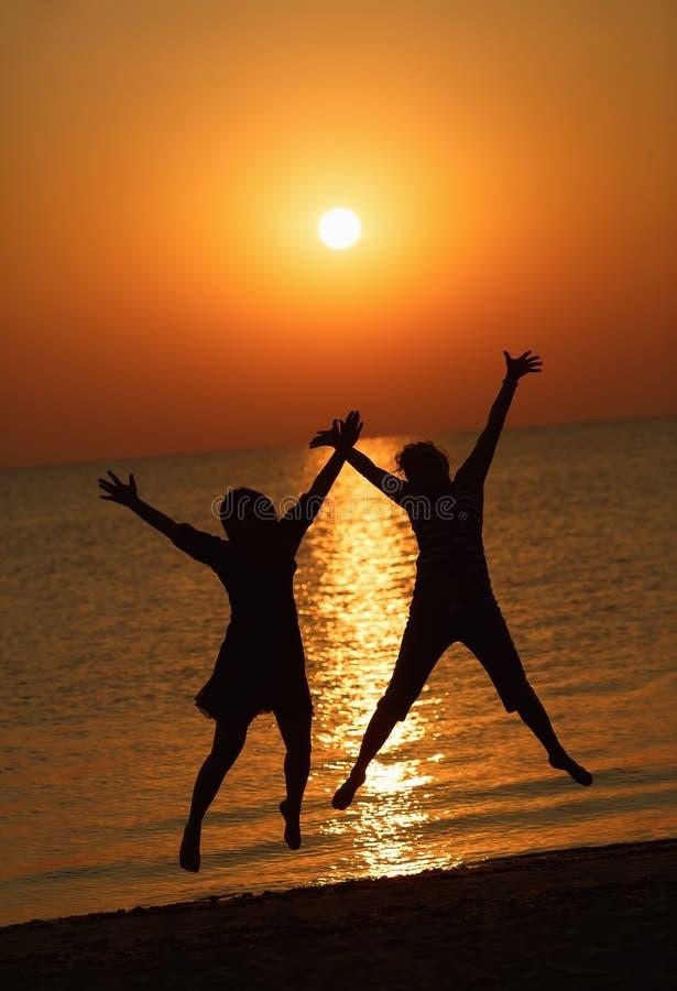 Las muchachas que saltan en un fondo del sol naciente imagenes de archivo