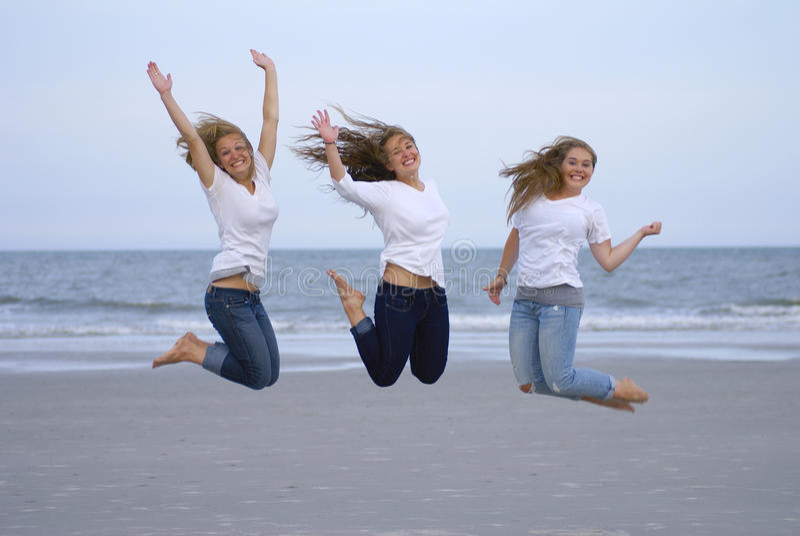 Las muchachas que saltan para la alegría en la playa foto de archivo libre de regalías