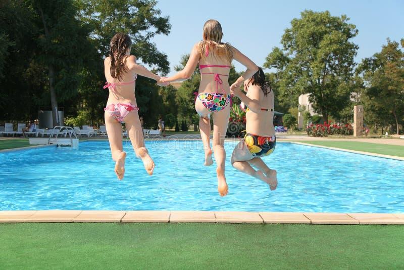 Las muchachas saltan en piscina imagenes de archivo