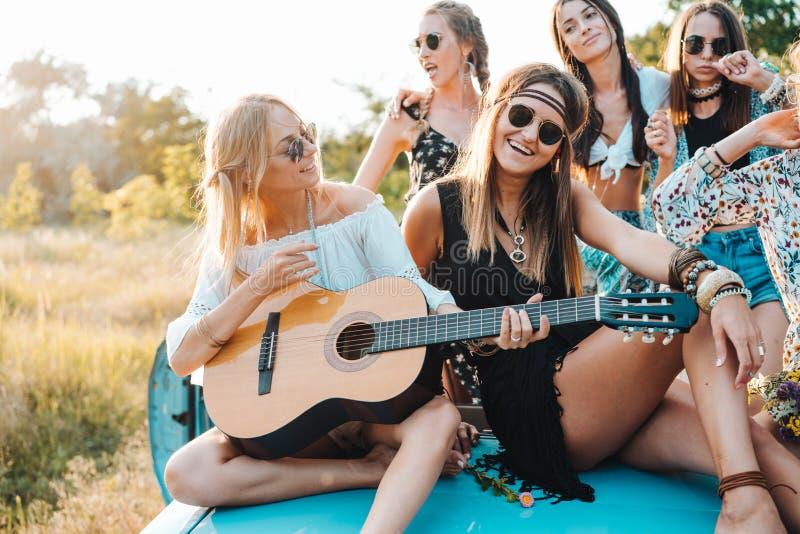 Las muchachas se están sentando en el tronco con una guitarra imagen de archivo