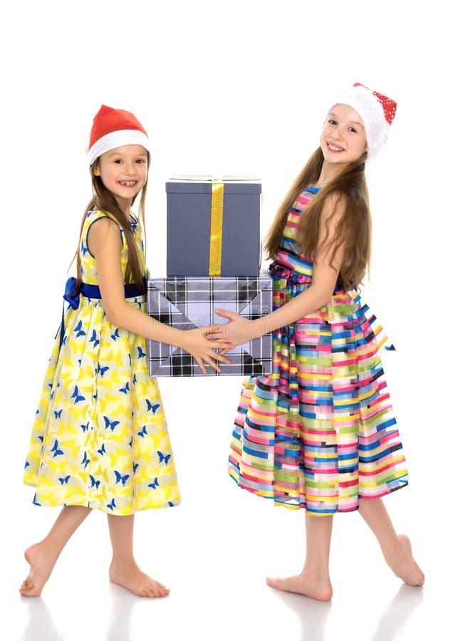 Las muchachas son hermanas en los sombreros y los presentes de Santa Claus foto de archivo libre de regalías