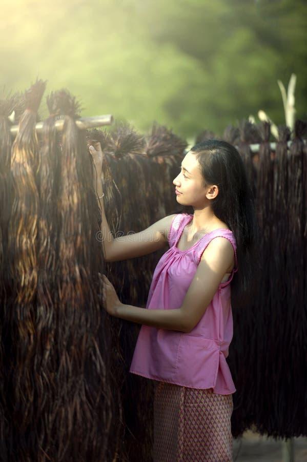 Las muchachas son materias textiles con el papiro la estera fotografía de archivo