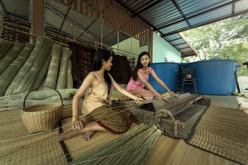 Las muchachas son materias textiles con el papiro la estera foto de archivo libre de regalías