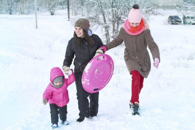 las muchachas y la madre entran adelante en la nieve que lleva a cabo las manos foto de archivo libre de regalías