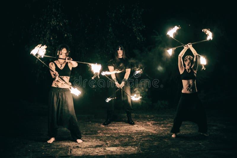 Las muchachas y los muchachos activos realizan los trucos para la demostración del fuego en la noche imagenes de archivo