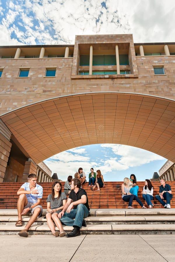 Las muchachas y los muchachos se est?n sentando en las escaleras debajo de edificios foto de archivo libre de regalías