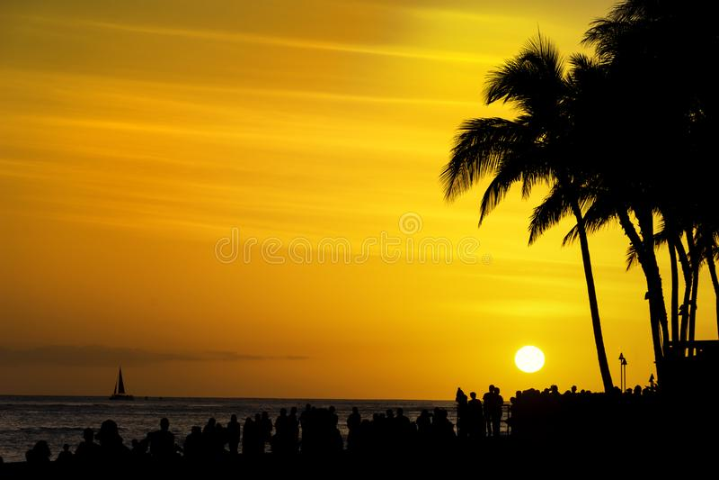 Las muchedumbres de turistas recolectan para mirar la puesta del sol en la playa Honolulu Oahu Hawaii los E.E.U.U. de Waikiki fotografía de archivo
