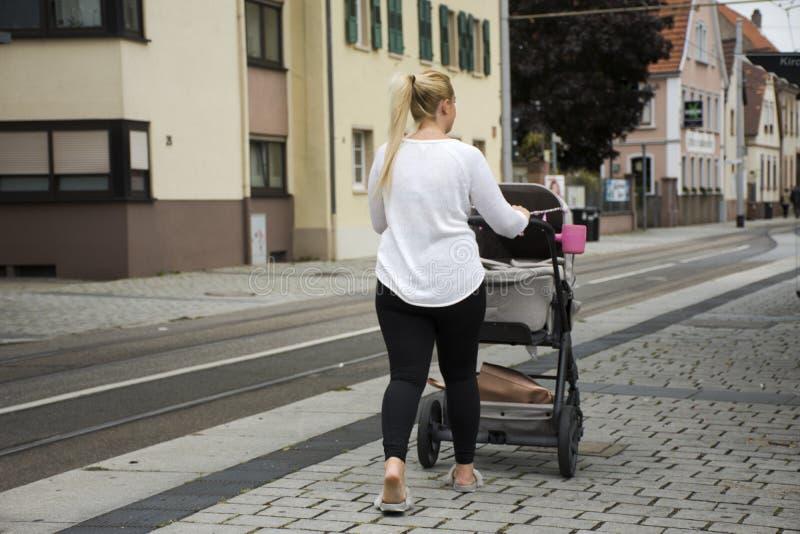 Las mujeres alemanas empujan el cochecito en la calle cerca de la estación del tranvía en Sandhausen fotos de archivo libres de regalías