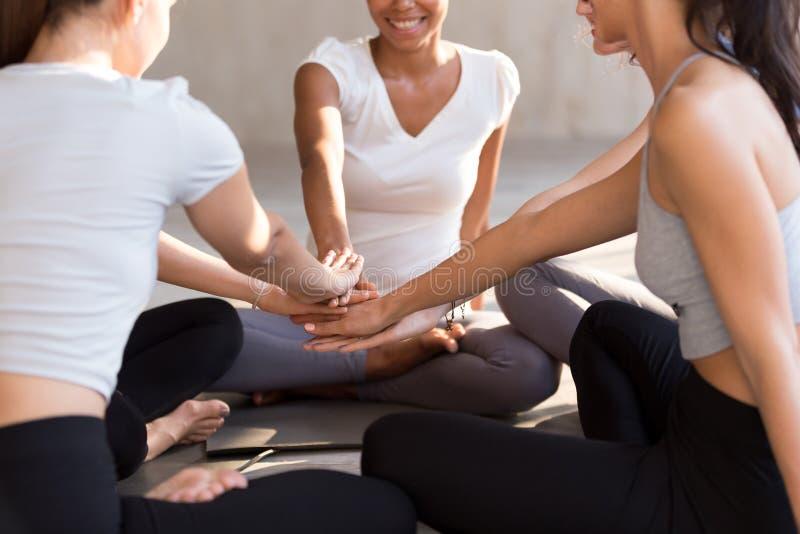 Las mujeres aptas emocionadas se unen a las manos que muestran la unidad en el entrenamiento foto de archivo