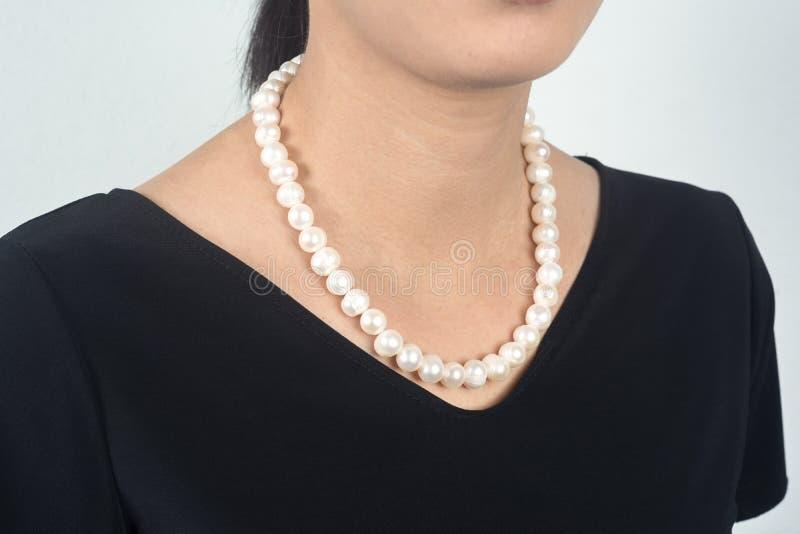 Las mujeres asiáticas del retrato pusieron el collar de la perla en vestidos negros imagen de archivo