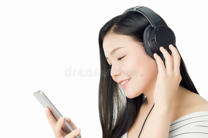 Las mujeres asiáticas están escuchando la música de los auriculares negros En un humor cómodo y bueno foto de archivo libre de regalías