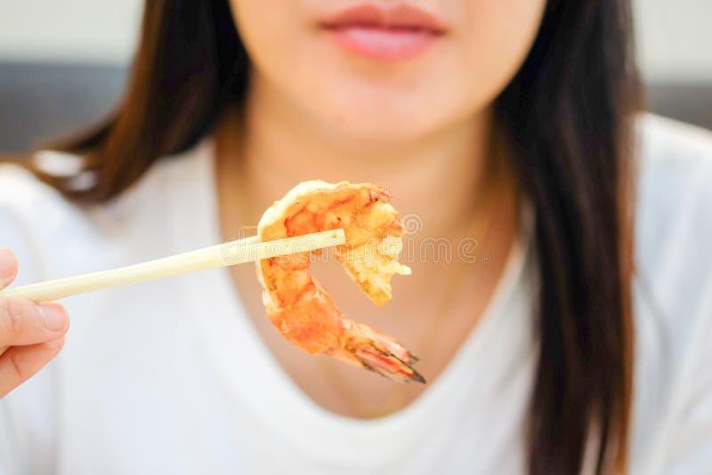 Las mujeres asiáticas están utilizando los palillos para coger el camarón imagen de archivo