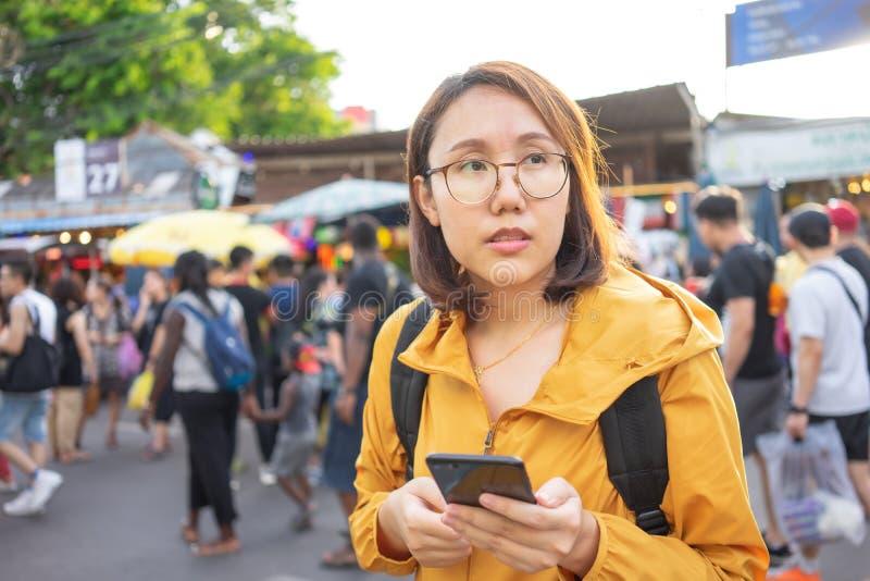 Las mujeres asiáticas hermosas del retrato se colocan para sostener smartphones en el mercado de Chatuchak en Tailandia Bangkok e foto de archivo