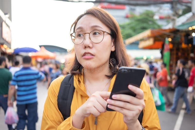 Las mujeres asiáticas hermosas del retrato se colocan para sostener smartphones en el mercado de Chatuchak en Tailandia Bangkok e imagen de archivo