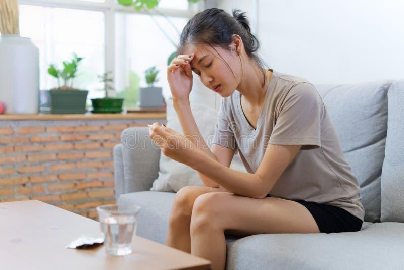 Las mujeres asiáticas jovenes en el sofá que se cierra los ojos están sufriendo de dolor de cabeza y tienen cierta fiebre foto de archivo libre de regalías