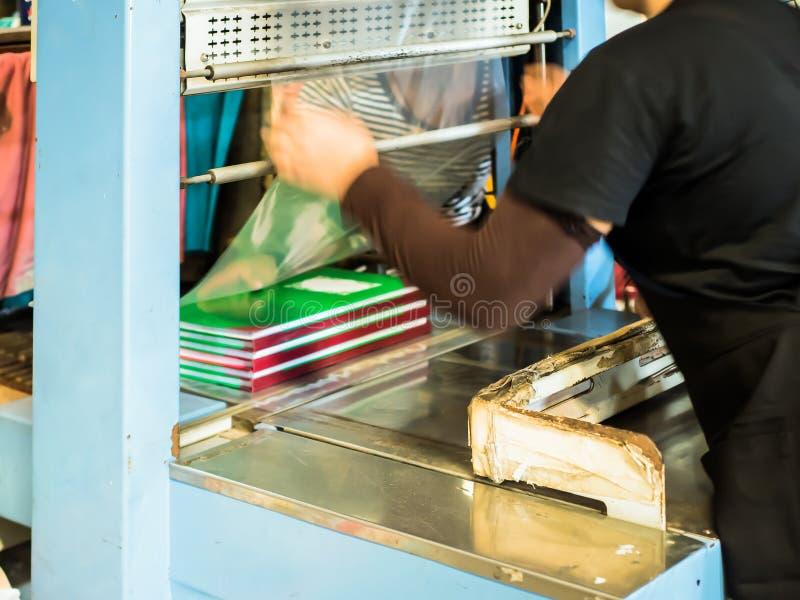 Las mujeres asiáticas que cubren el plástico para el libro hacen listo para embalar foto de archivo libre de regalías