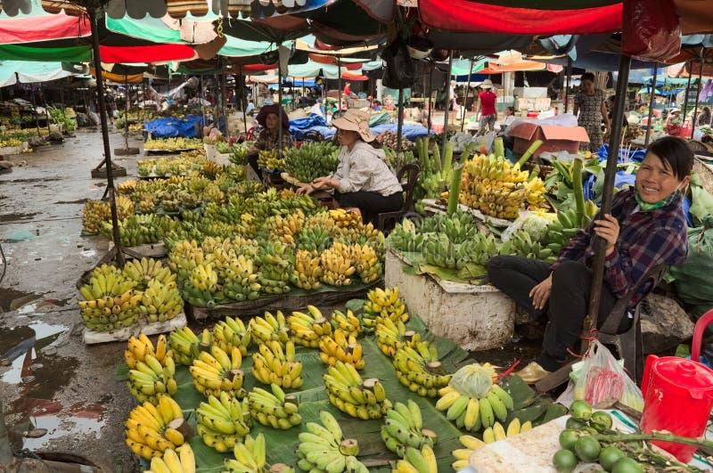 Las mujeres asiáticas que venden el plátano dan fruto en el mercado callejero imagenes de archivo