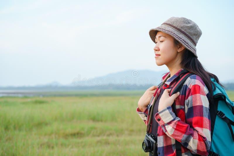 Las mujeres asiáticas se están cerrando los ojos y están disfrutando de la naturaleza en las montañas y el fondo del cielo Una ch imagenes de archivo