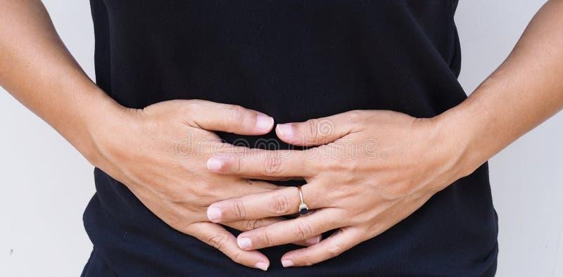 Las mujeres asiáticas tienen dolor abdominal imagen de archivo