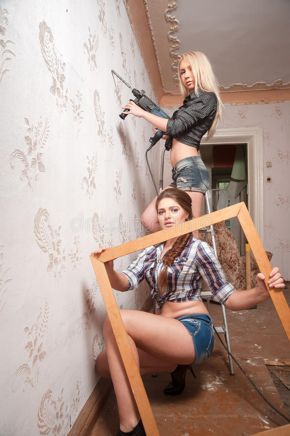 Las mujeres atractivas reparan en el apartamento imagen de archivo