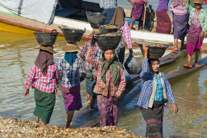 Las mujeres birmanas descargan una gabarra con los guijarros del río imágenes de archivo libres de regalías
