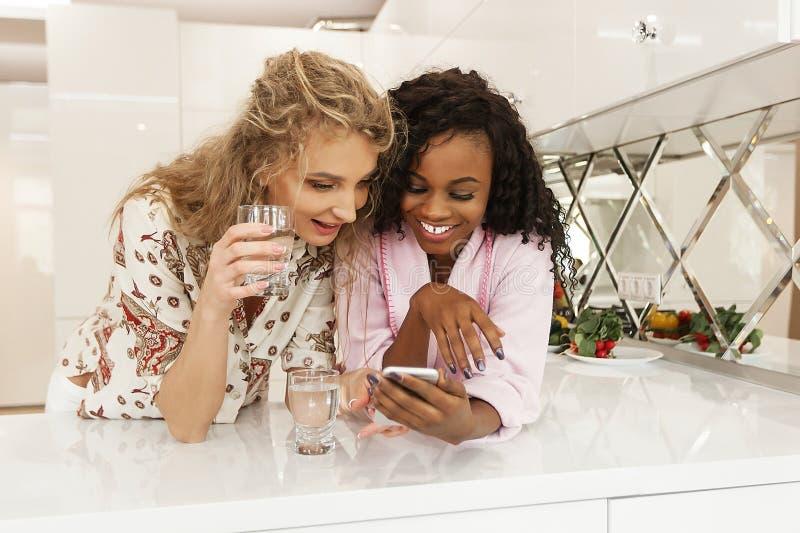Las mujeres blancos y negros que miran la pantalla del teléfono que hace una pausa la cocina emergen imagenes de archivo
