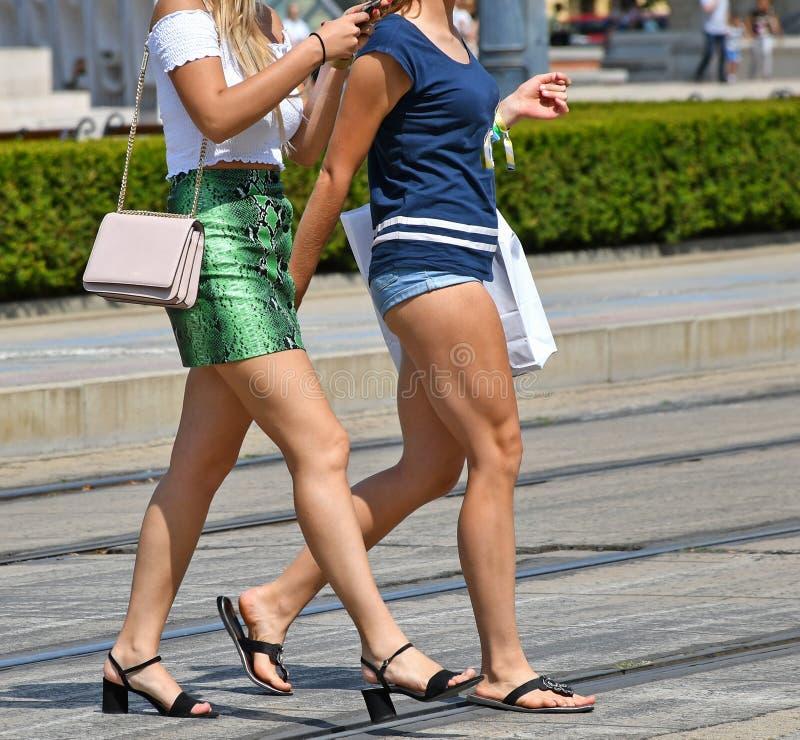 Las mujeres bonitas están caminando en la calle de la ciudad foto de archivo libre de regalías
