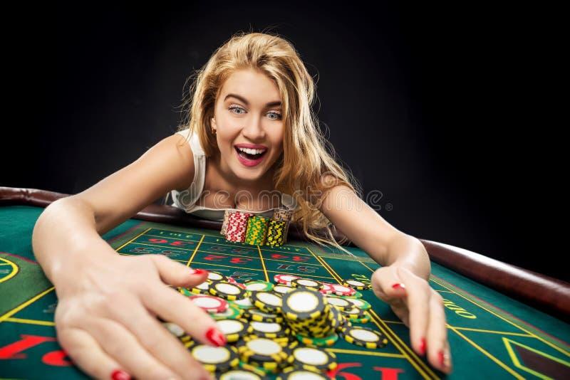 Las mujeres bonitas jovenes que juegan la ruleta ganan en el casino foto de archivo