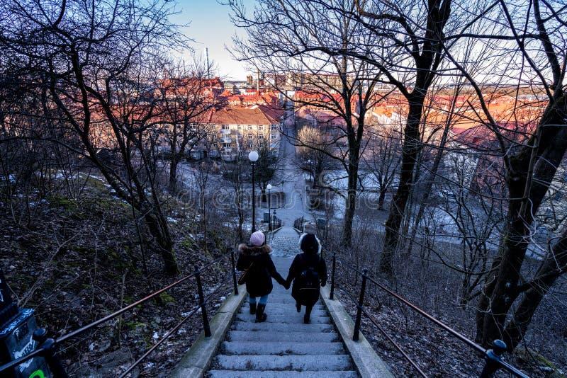 Las mujeres caminan abajo de las escaleras que pasan por alto Goteburgo en la puesta del sol imagenes de archivo