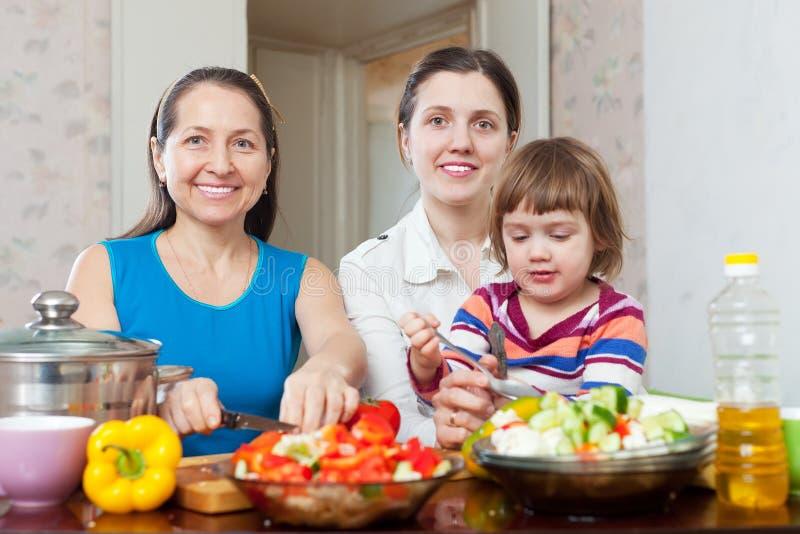 Las mujeres cocinan verduras, mientras que niño que come la ensalada imagen de archivo libre de regalías
