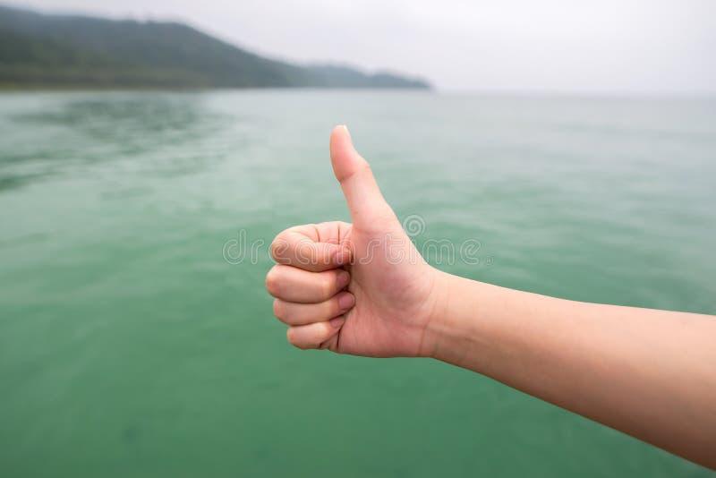 Las mujeres dan con el pulgar para arriba en el mar verde imagen de archivo