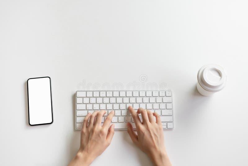 Las mujeres dan están mecanografiando el teclado y el smartphone, taza de café en el escritorio fotografía de archivo libre de regalías