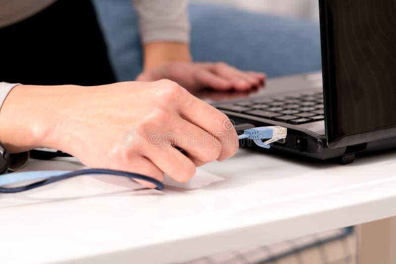Las mujeres dan están tapando en el cable de lan al puerto del ordenador portátil foto de archivo