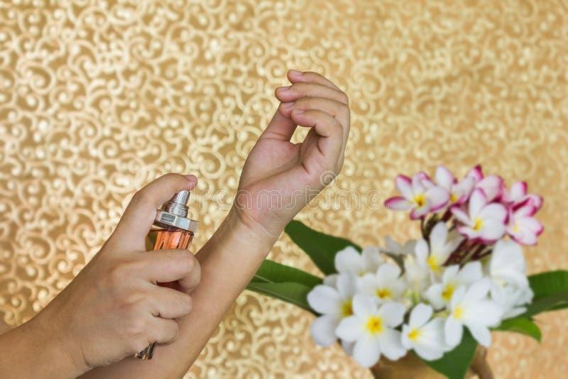 Las mujeres dan perfume de rociadura en la muñeca con las flores en florero y cl imagen de archivo libre de regalías