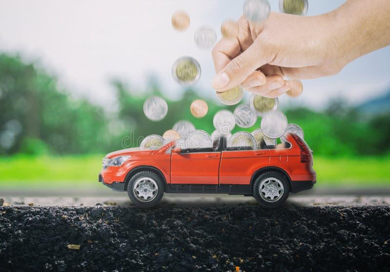 Las mujeres dan poner monedas en un coche rojo para llenarse El concepto de ahorro para comprar el nuevo coche imagen de archivo