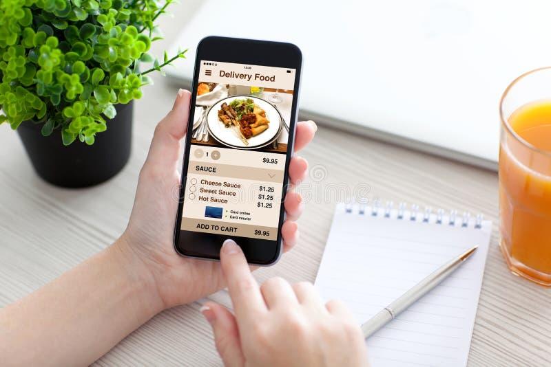 Las mujeres dan sostener el teléfono con la comida de la entrega del app en la pantalla imagenes de archivo