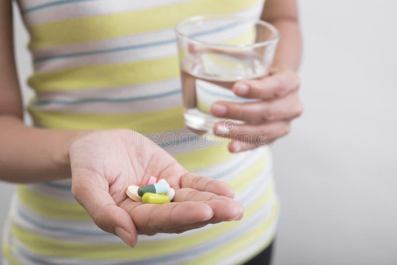 Las mujeres dan sostener el vidrio de agua están tomando la medicina fotografía de archivo libre de regalías