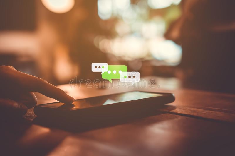 Las mujeres dan usando smartphone que mecanografían, charlando la conversación en iconos de la caja de la charla surgen imagenes de archivo
