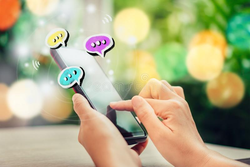 Las mujeres dan usando smartphone que mecanografían, charlando la conversación en iconos de la caja de la charla surgen fotos de archivo