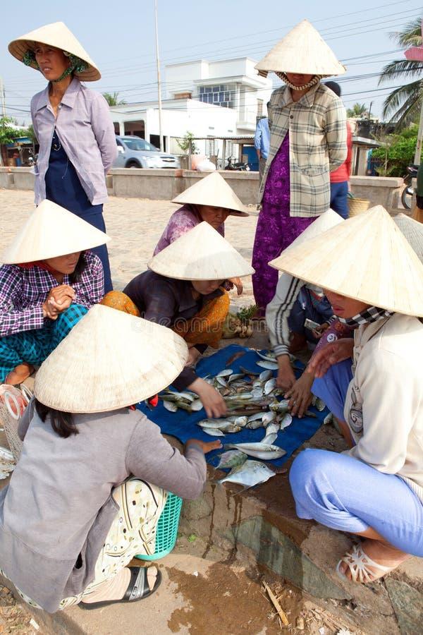 Las mujeres de bambú del sombrero eligen pescados para vender en mercado foto de archivo libre de regalías