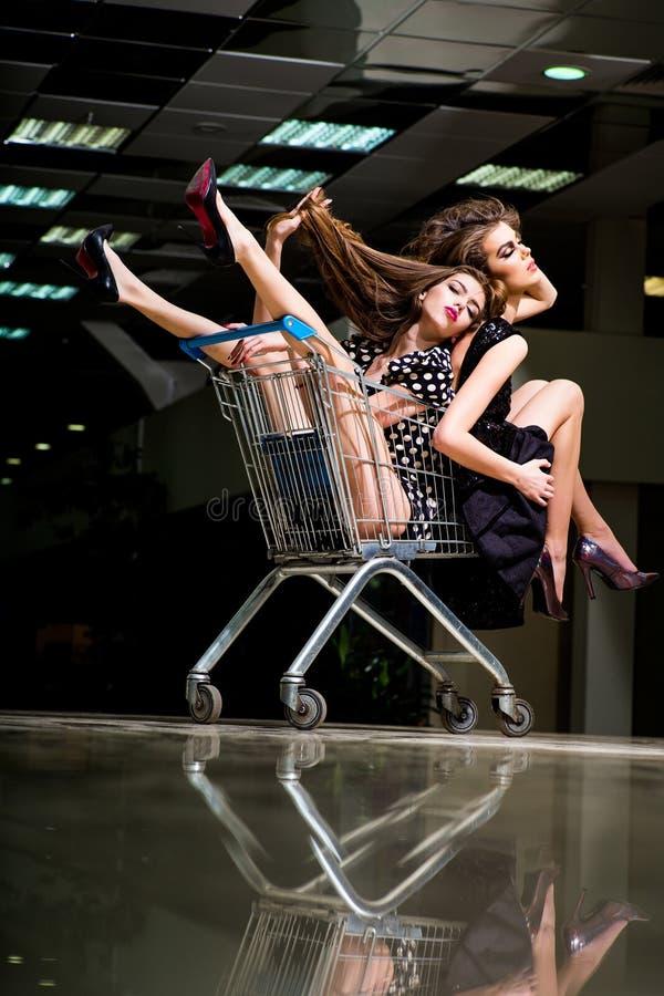 Las mujeres de las compras se sientan en carro de la carretilla imagen de archivo libre de regalías